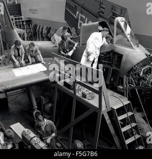 historical, 1950s, aircraft engineering or technical students working on an aircraft's engine under supervision, - Stock Photo
