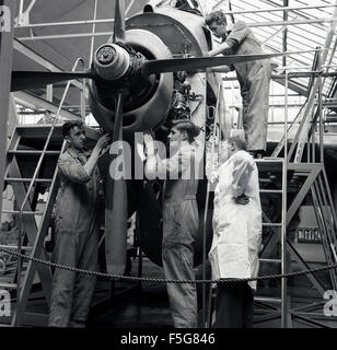 historical, 1950s, aircraft engineering or technical students working on an aircraft's propeller under supervision. - Stock Photo