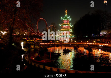 The Dragon Boats in the lake in front of the Japanese Tower restaurant and rides at night in Tivoli gardens on a - Stock Photo