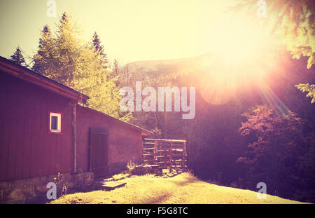 Retro vintage stylized mountain shelter against sun with flare effect. - Stock Photo