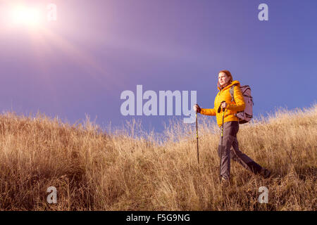 Female hiker walking on grassy hill - Stock Photo