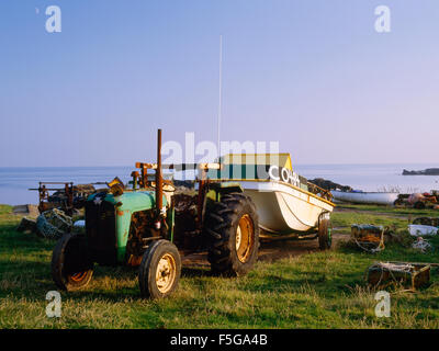 Fishing boat drawn up out of the sea by old tractor and trailer, Cafn, Bardsey Island, North Wales, UK - Stock Photo