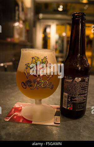 A bottle of Cuveé des Trolls Belgian craft beer in its branded glass on a zinc, Bar du Midi in Amiens, Somme, Picardie, - Stock Photo