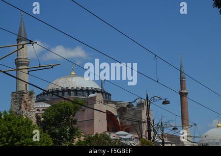 Hagia Sophia Church then Mosque now museum visible behind the tram wires showing the church dome and two minarets. - Stock Photo