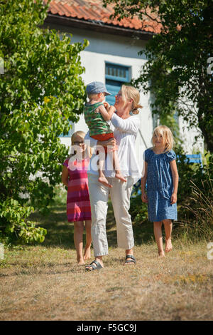 Sweden, Gotland, Faro, Mother with daughters (8-9, 10-11) and son (2-3) in backyard - Stock Photo