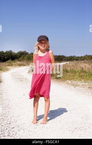 Sweden, Gotland, Holmhallar, Girl (8-9) standing on dirt road - Stock Photo
