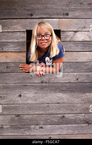 Sweden, Gotland, Faro, Girl (10-11) looking out of tree house window - Stock Photo