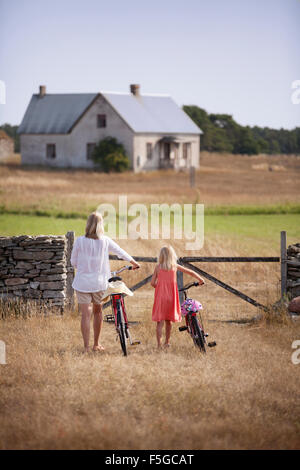 Sweden, Gotland, Faro, Mother and daughter (8-9) wheeling bicycles toward farm gate - Stock Photo