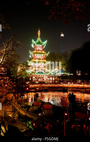 The Dragon Boats in the lake in front of the Japanese Tower restaurant in the Tivoli gardens on a dark Halloween - Stock Photo