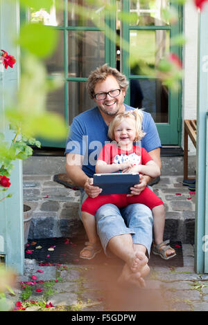 Sweden, Skane, Mossby, Portrait of daughter with father holding tablet pc - Stock Photo