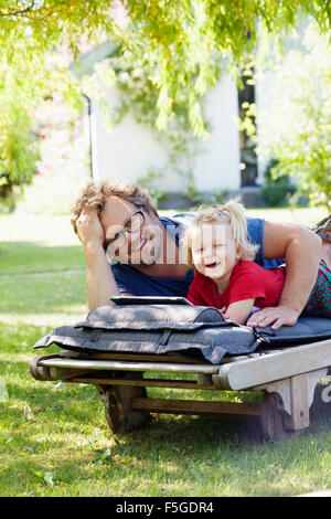 Sweden, Skane, Mossby, Portrait of daughter with father lying on deckchair and using tablet pc - Stock Photo