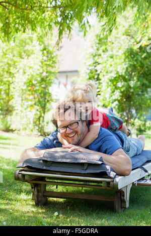 Sweden, Skane, Mossby, Portrait of daughter with father lying on deckchair - Stock Photo