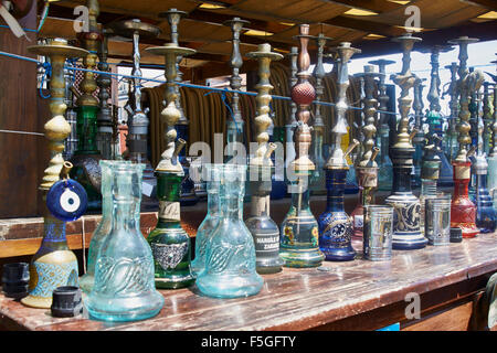 Turkish smoking pipes (hookah) lined up on outdoor bar counter. - Stock Photo
