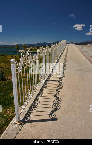 Road and pedestrian bridge with decorative white railings and shadows. - Stock Photo