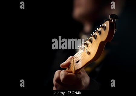 Guitarist on stage - closeup with selective focus on guitar head - Stock Photo