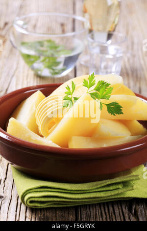 Dish of boiled potatoes and curl of butter - Stock Photo