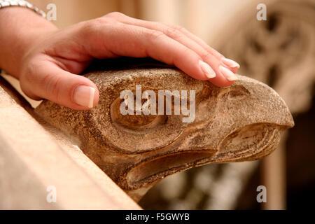 A woman hand rest over stone gargoyle. Toledo, Spain - Stock Photo