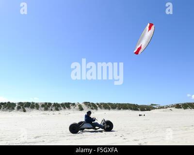 Man riding kite buggy very fast on beach - Stock Photo