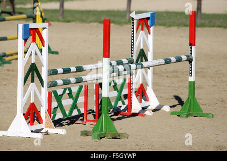 Colorful oxer on the ground for jumping horses as a background - Stock Photo