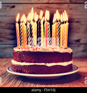 a cake topped with some lit candles before blowing out the cake, on a rustic wooden table, with a filtered effect - Stock Photo