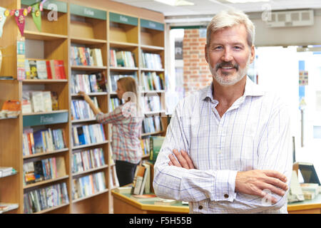 Portrait Of Male Bookstore Owner With Customer In Background - Stock Photo