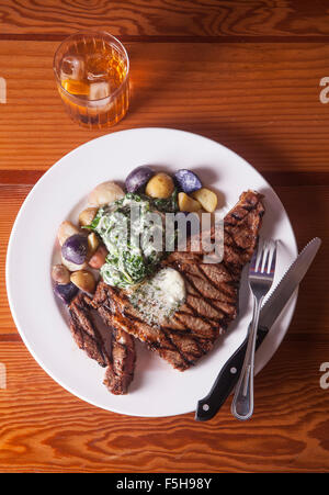 overhead view of steak with potatoes and spinach knife and fork and cocktail on wood table - Stock Photo