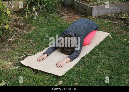 A woman in child's pose on a yoga mat in a garden. - Stock Photo