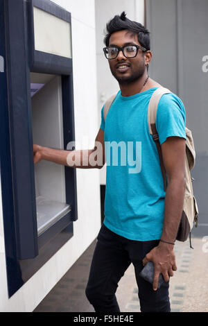 young man at the atm withdrawing cash - Stock Photo