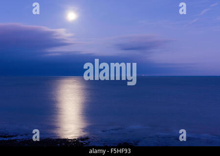 Super moon shinning in a mauve blue sky over a clam sea, the English Channel, off the kent Coast at Ramsgate, with - Stock Photo