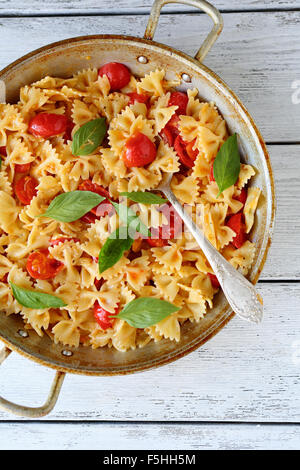 pasta with tomatoes and basil in old pan - Stock Photo
