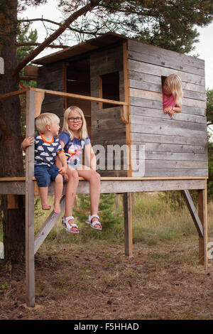 Sweden, Gotland, Faro, Boy (2-3) and sisters (8-9, 10-11) sitting on porch of tree house - Stock Photo