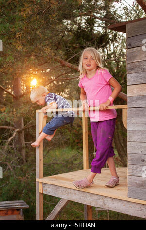 Sweden, Gotland, Faro, Girl (8-9) with brother (2-3) at tree house porch - Stock Photo