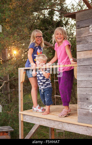 Sweden, Gotland, Faro, Girls (8-9, 10-11) with brother (2-3) at tree house porch - Stock Photo