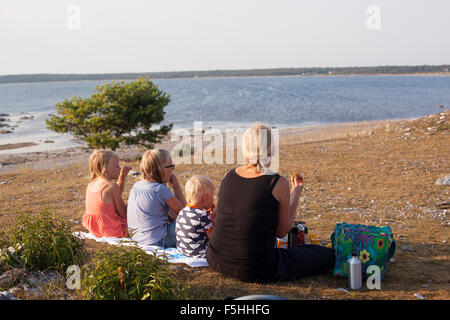 Sweden, Gotland, Faro, Gamle hamn, Family having picnic at beach - Stock Photo