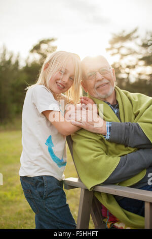 Sweden, Gotland, Faro, Portrait of grandfather with his granddaughter (8-9) in back yard - Stock Photo