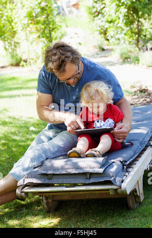 Sweden, Skane, Mossby, Daughter with father sitting on deckchair and using tablet pc - Stock Photo