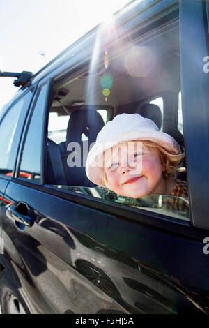 Sweden, Gotland, Visby, Portrait of girl sitting in car - Stock Photo