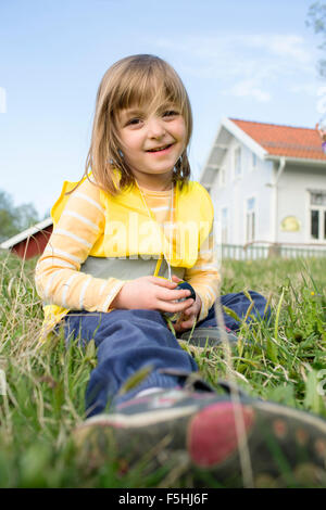 Sweden, Vastergotland, Olofstorp, Bergum, Portrait of girl (4-5) sitting in grass - Stock Photo