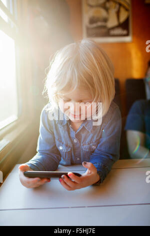 Sweden, Girl (2-3) using smart phone on train - Stock Photo