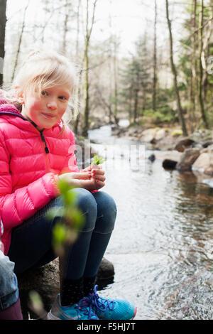 Sweden, Vastergotland, Vattlefjall nature reserve, Portrait of girl (10-11) by river - Stock Photo
