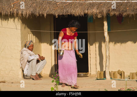 Couple of Tharu people in traditional adobe house in terai, Nepal - Stock Photo