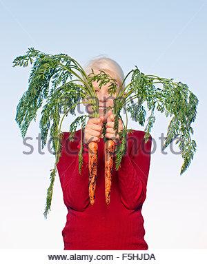 Teenage girl (16-17) holding bunch of carrots - Stock Photo