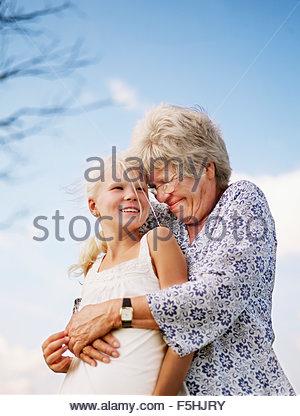 Denmark, Portrait of grandmother embracing granddaughter (10-11) - Stock Photo