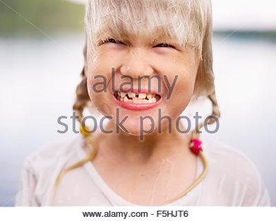 Sweden, Stockholm Archipelago, Uppland, Arholma, Portrait of girl (6-7) smiling - Stock Photo