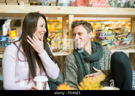 Sweden, Man and woman laughing in shop - Stock Photo