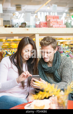 Sweden, Man and woman using smart phone in shop - Stock Photo