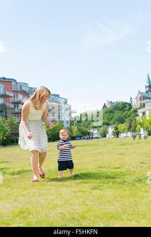 Sweden, Sodermanland, Nacka, Finnboda Hamn, Mother with baby boy (18-23 months) in park - Stock Photo