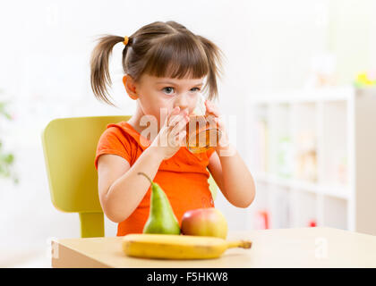 Smiling child girl sitting on the table with fruits and drinking juice in nursery - Stock Photo