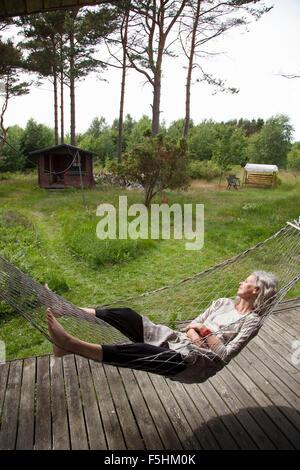 Sweden, Bohuslan, Woman relaxing in hammock - Stock Photo