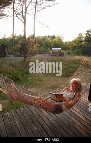 Sweden, Bohuslan, Woman reading book in hammock - Stock Photo